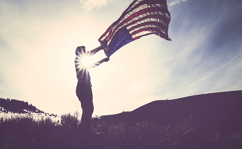 A man tosses the American flag as the sun dawns. This image was used on a post about why conservative Christians fear the Syrian refugees.
