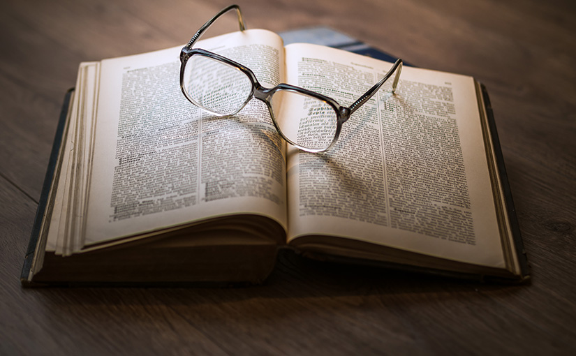 An open antique book on a wooden table with a pair of reading glasses resting on top of it. In this post, S. Wyatt Young asks an important question: What is the Bible?