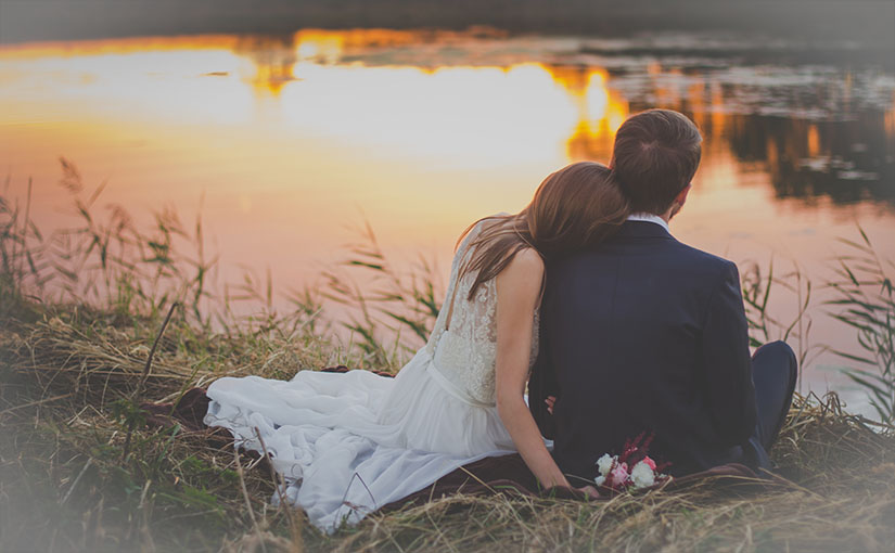 A married couple sits on the edge of a pond at sunset, wearing their wedding garb.