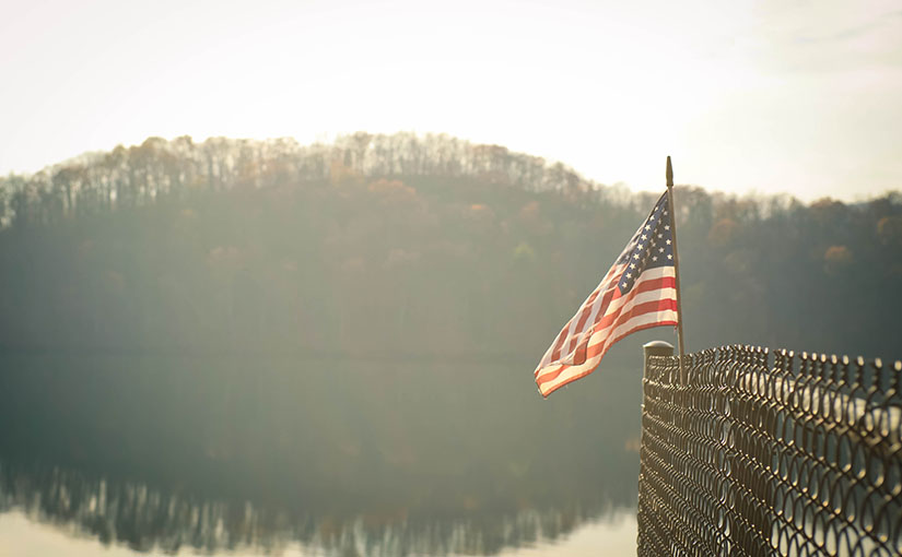 An american flag atop a chainlink fence as the sun rises over a hilltop. In the wake of the 2016 election, the depression was palpable, but it was more than just defeat. People felt as though they'd lost someone, or something. In this post, writer and author S. Wyatt Young expounds on what that thing is.