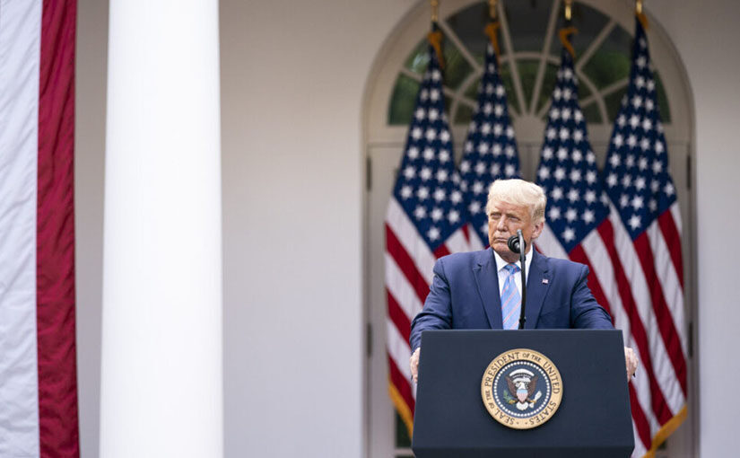 President Donald Trump stands at a podium outside the White House, flanked by American flags.